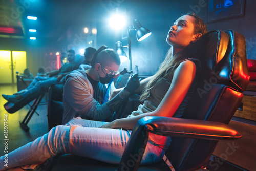 Photo Young Woman Getting Tattoos In Beauty Parlor With Tattooist Working