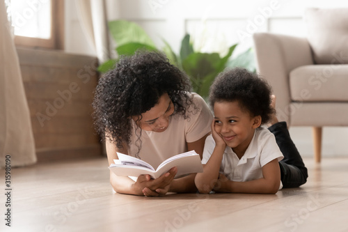 Cute curly black boy listening to funny stories. Canvas Print