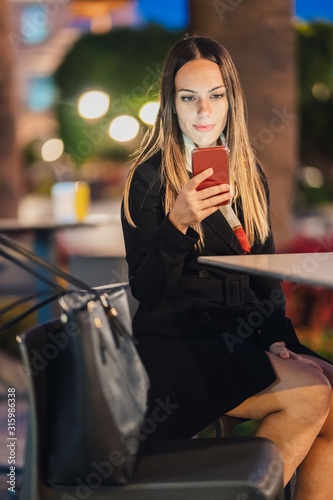 Fotomural business woman sitting on a terrace at night checking her mobile phone
