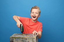 Child Joy, Play With DIY Tools. The Child Plays With A Screwdriver. Portrait Of A Boy On A Blue Background.