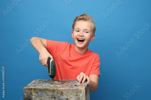 Fototapeta Child joy, play with DIY tools. The child plays with a screwdriver. Portrait of a boy on a blue background. obraz