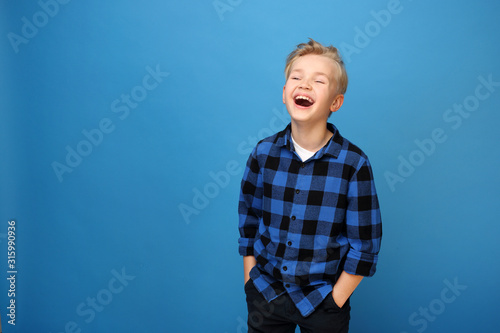 Obraz Happy child, laughing boy. Happy, smiling boy on a blue background expresses emotions through gestures. - fototapety do salonu