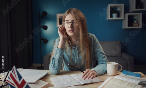 Fotografie, Obraz  Concentrated lady studying English listening audio lesson in earbuds sitting at