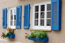 Two Windows With White Wooden Frames, Blue Shutters And Decorative Flower Boxes. Image Of Trendy Decor, Comfort, Beautification.