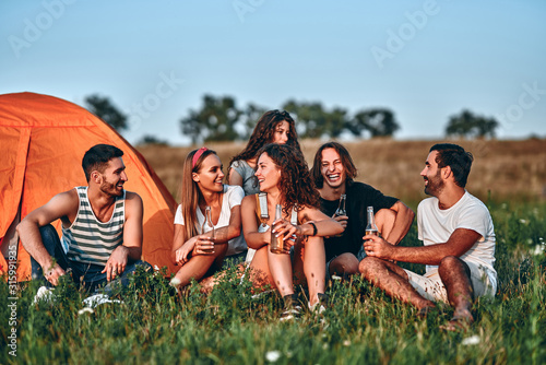 Group of friends having fun outside tents on camping holiday Wallpaper Mural