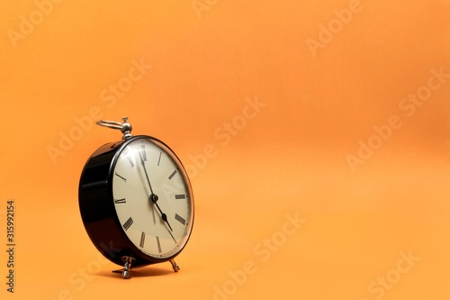 Cuadros en Lienzo A wide portrait of a small old fashioned antique alarm clock with roman numbers on the dial on an orange background