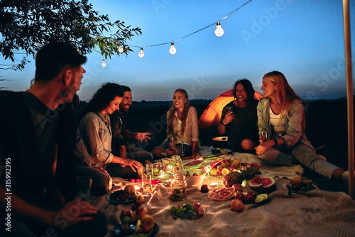 Obraz Group people rest near camping tent in evening time - fototapety do salonu
