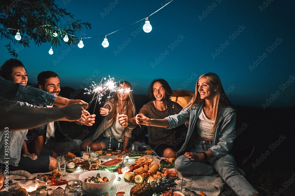 Fototapeta Group of friends enjoying out with sparklers. Young men and women enjoying with fireworks
