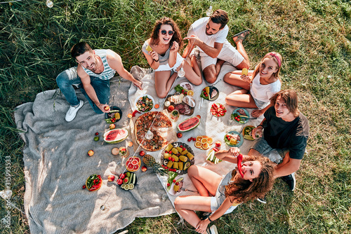 Young people enjoying picnic in park on summer day Fotobehang
