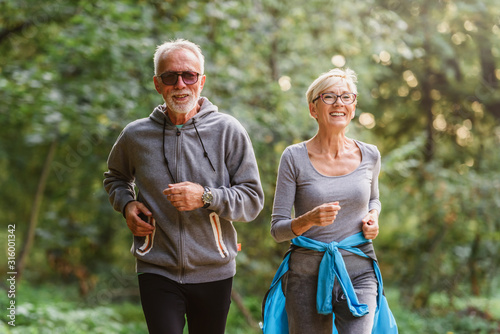 Cheerful active senior couple jogging in the park Canvas Print