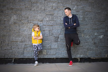 Full Length Of Father And Son Talk While Leaning On Wall With Crossed Arms.
