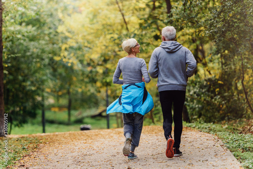 Cheerful active senior couple jogging in the park Wallpaper Mural