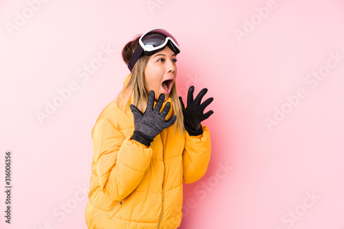 Photo Young caucasian woman wearing a ski clothes in a pink background shouts loud, keeps eyes opened and hands tense