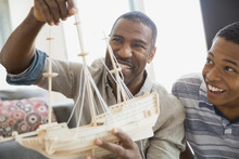 Father And Son Building Ship Model At Home