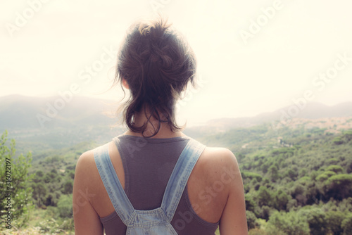 Young hipster woman from behind admiring panorama from hill overseeing bay in Tu Canvas Print