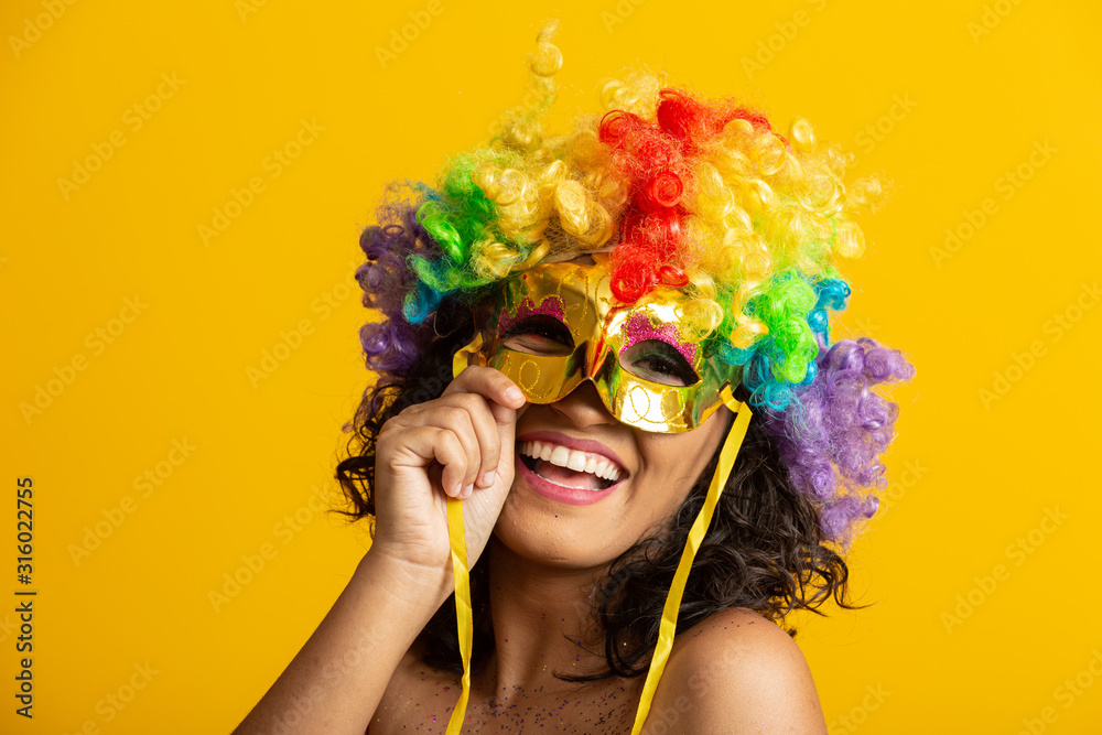 Fototapeta Beautiful woman dressed for carnival night. Smiling woman ready to enjoy the carnival with a colorful wig and mask