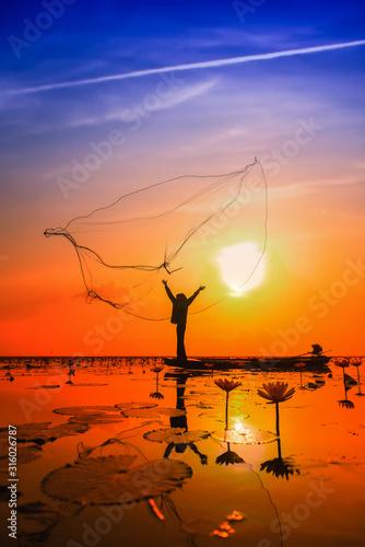 Asian Fisherman on boat fishing at lake Wall mural