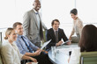 Group of business people looking at colleague while sitting in conference room