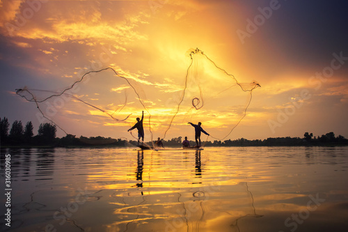 Fototapeta Asian Fishermen on boat fishing at lake, Thailand countryside