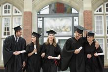 College Graduates Walking With Diplomas
