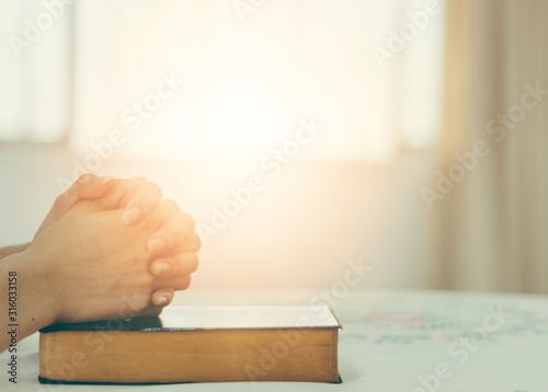 The hand of a Christian woman rests on the Bible to pray for God. Fototapet