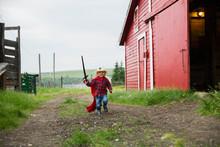 Portrait Of Boy With Sword Outside Barn