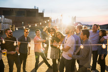 Friends With Sparklers Enjoying Urban Rooftop Party
