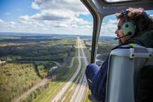 Pilot In Helicopter Flying Over Landscape