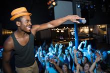 DJ With Microphone Above Cheering Nightclub Crowd