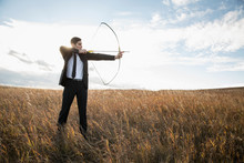 Businessman Taking Aim With Bow And Arrow In Field