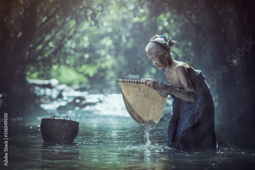 Cuadros en Lienzo Old Asian woman working in creek, Thailand countryside