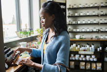 Woman Browsing Essential Oils In Apothecary Shop