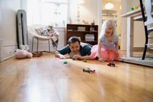 Father And Daughter Racing Toy Cars On Floor