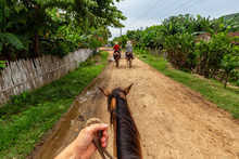 Trinidad, Cuba. Horseback Riding On A Dirty Trail In The Country Side Near A Small Cuban Town During A Vibrant Sunny Day.