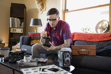 Man Repairing Antique Camera In Living Room