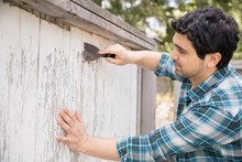 Man Chipping Paint From Wooden Fence