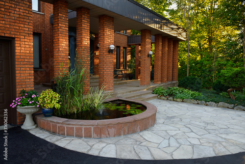 Tablou Canvas Front entrance with pond and stone veranda on red brick house with pillars