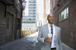 Businessman with coffee walking in urban alley
