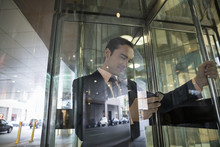 Businessman Texting With Cell Phone In Revolving Doors