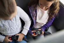 Schoolgirls Fastening Seat Belts On School Bus
