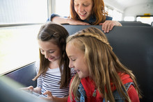 Schoolgirls Texting With Cell Phone On School Bus
