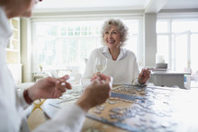 Senior Women Assembling Jigsaw Puzzle At Dining Table