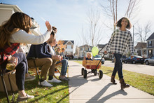 Neighbors Waving At Girl Pulling Friend In Wagon
