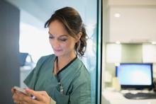 Nurse Texting At Nurses Station
