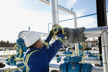 Male Worker Turning Valve On Gas Plant Pipeline