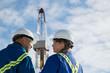 Workers talking below drilling rig