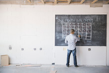 Business Owner At Blackboard Calendar In New Office