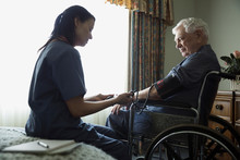 Home Caregiver Checking Blood Pressure For Senior Man In Wheelchair