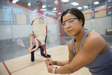 Serious Women Playing Squash On Indoor Court