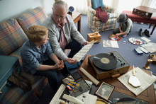 Grandfather And Grandson Looking Through Old Memorabilia